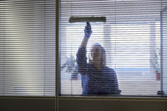 Maid cleaning and wiping window in office