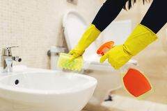 Maid cleans the bidet with a cleaning spray. Maid hands in rubber gloves cleans the bidet with a cleaning spray, hotel restroom interior on background stock photo