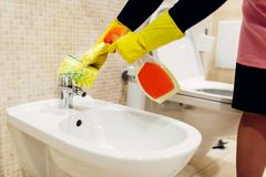 Maid cleans the bidet with a cleaning spray. Maid hands in rubber gloves cleans the bidet with a cleaning spray, hotel restroom interior on background royalty free stock photo