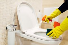Maid cleans the bidet with a cleaning spray. Maid hands in rubber gloves cleans the bidet with a cleaning spray, hotel restroom interior on background stock photography