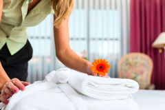Maid doing room service in hotel. She is making up the beds Stock Photo
