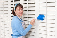 Maid dusting shutters Stock Image