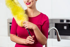 Maid with feather duster. In the kitchen stock photos
