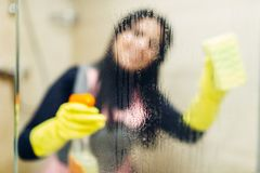 Maid in gloves cleans glass with a cleaning spray. Hotel bathroom interior on background. Professional housekeeping, charwoman stock photo