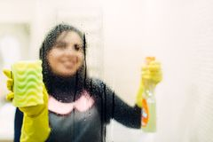Maid in gloves cleans glass with a cleaning spray. Hotel bathroom interior on background. Professional housekeeping, charwoman stock images