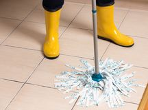 Housekeeper mopping tiled floor. Maid in gumboots mopping tiled floor. Housekeeping and home hygiene concept Stock Photos