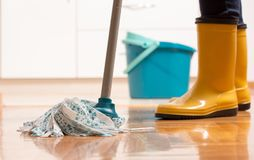 Housekeeper mopping tiled floor. Maid in gumboots mopping tiled floor in kitchen. Housekeeping and home hygiene concept Royalty Free Stock Photo