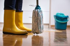 Housekeeper mopping tiled floor. Maid in gumboots mopping tiled floor in kitchen. Housekeeping and home hygiene concept Stock Photography