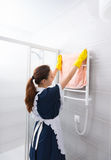 Maid hanging towel on rack in bathroom Royalty Free Stock Image