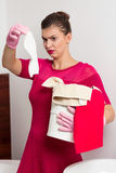 Maid holding dirty sock Royalty Free Stock Image