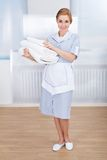 Maid holding stack of towels Royalty Free Stock Photos