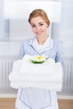Maid holding stack of towels Royalty Free Stock Photo