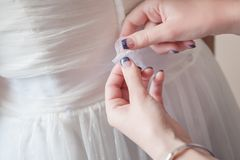 A maid of honor assists with tying the bride`s ribbon sash on her gown. stock photo