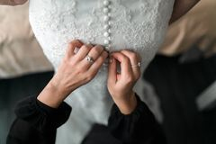 Maid of honor helping the bride with her dress. Closeup portrait of a maid of honor helping the bride with her dress Royalty Free Stock Images