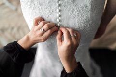 maid of honor helping the bride with her dress Stock Photography