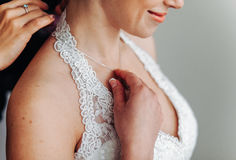 maid of honor helping the bride with her dress Stock Image