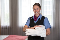Maid in a hotel posing with towels in bedroom Royalty Free Stock Image