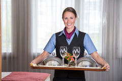 Maid in a hotel posing with tray in bedroom Stock Photo