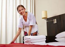 Maid in hotel room making bed Stock Image