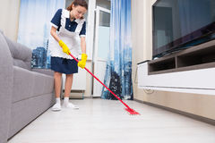Maid or housekeeper cleaning a living room. Maid or housekeeper in a neat white apron cleaning a living room floor with a colorful red mop, low angle view at Royalty Free Stock Photos