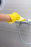 Maid or housewife cleaning the tap in a shower Royalty Free Stock Photography