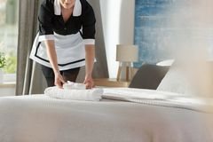 Maid laying fresh towels. Young maid laying fresh towels on a bed in a hotel room royalty free stock photo