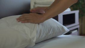 Maid making bed and adjusting pillows in five star hotel, impeccable service