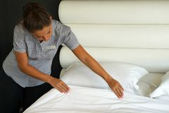 Maid Making Bed. In hotel room Royalty Free Stock Images