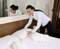 Maid making bed in hotel room. Smiling Royalty Free Stock Photos