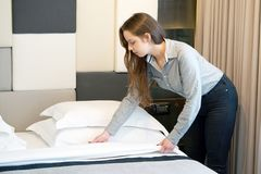 Maid Making Bed. In hotel room Stock Photos