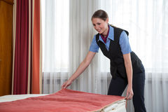 Maid making the bed in a hotel room Royalty Free Stock Photos