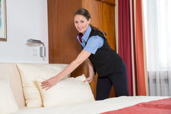 Maid making the bed in a hotel room Stock Image