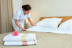 Maid making bed in hotel room. Hotel room service. Young maid changing bedclothes in a room Royalty Free Stock Image