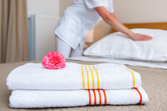 Maid making bed in hotel room. Hotel room service. Young maid changing bedclothes in a room Stock Photo