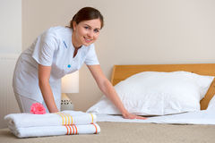 Maid making bed in hotel room. Hotel room service. Young maid changing bedclothes in a room Stock Photos