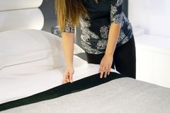 Maid Making Bed. In hotel room Royalty Free Stock Image