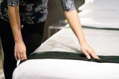 Maid Making Bed. In hotel room Royalty Free Stock Photography