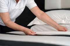 Maid Making Bed. In hotel room Stock Photo