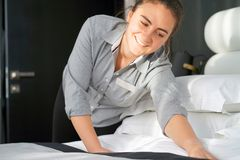 Maid Making Bed. In hotel room Stock Image