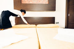 Maid Making A Hotel Room. Young happy maid making a hotel room Stock Photos
