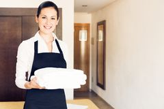 Maid Making A Hotel Room. Young happy maid cleaning up a hotel room Royalty Free Stock Photos