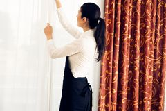 Maid Making A Hotel Room. Young happy maid cleaning up a hotel room Stock Image