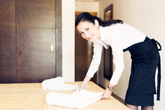 Maid Making A Hotel Room. Young maid is making up the hotel room Stock Photo