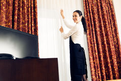 Maid Making A Hotel Room. Young maid is making up the hotel room Royalty Free Stock Images