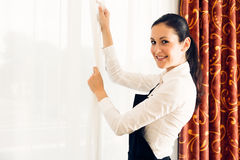 Maid Making A Hotel Room. Young maid is making up the hotel room Royalty Free Stock Photography