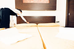 Maid Making Up A Hotel Room. Young happy maid is making up the hotel room Stock Image