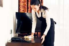 Maid Making Up A Hotel Room. Young happy maid is making up the hotel room Stock Photography