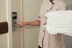 Changing linen. Maid opening door of hotel room to change sheets and towels Royalty Free Stock Image