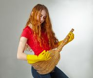 Cheerful housewife playing on her guitar broom. The maid plays on the broom as if she has a guitar in her hands Royalty Free Stock Photos