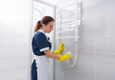 Maid plugging testing heated towel rack Stock Photo